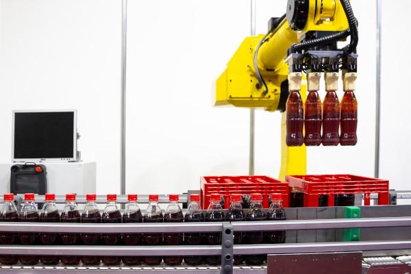 Żółty robot paletyzujący w fabryce