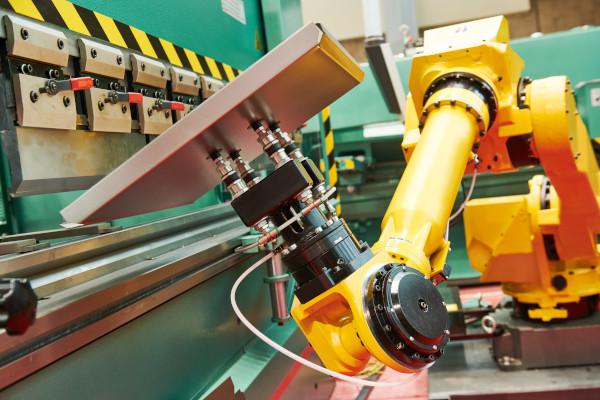 Pracujące żółte ramię robota trzymające płytę
